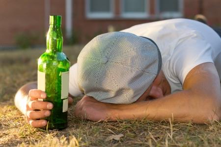 boozer: Drunk Caucasian man sleeping on the ground holding a bottle of white wine