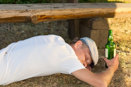 incapacitated: Alcoholic man passed out on the ground unconsciously next to a bench in the park
