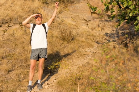 Male backpacker standing waving on a mountains slope with a broad smile to show his enjoyment of hiking in nature in the summer sunshine photo