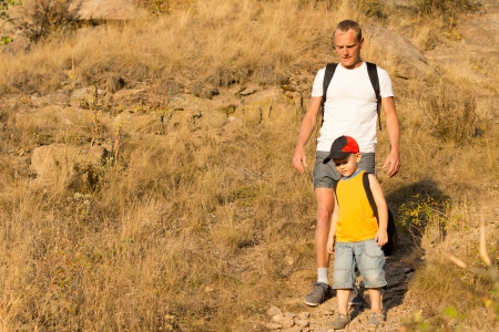 Father hiking with his small son descending a steep mountain trail wearing backpacks with copyspace photo