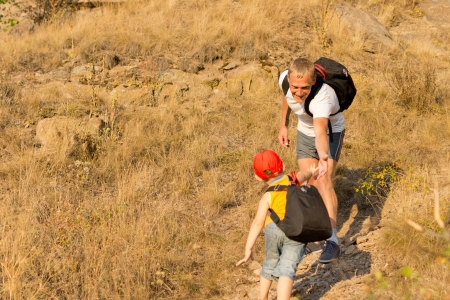 Young boy climbing a mountain with his father being helped up the steep slope with his little backpack on his back, with copyspace photo