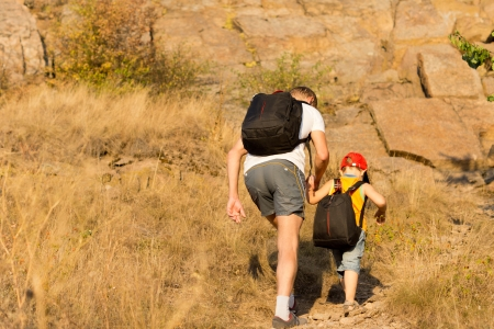 footing: Father and son wearing backpacks hiking on a mountain holding hands to prevent the young boy from losing his footing Stock Photo