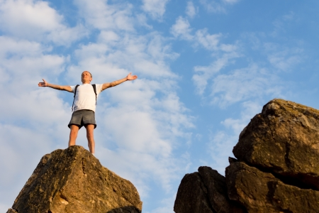 outspread: Jubilant backpacker on top of a mountain standing with his arms outspread against a cloudy blue sky in summer sunshine