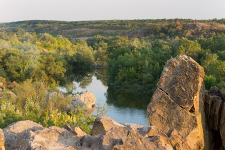 forested: Nature image with a watercourse passing through a forested green area and cliffs