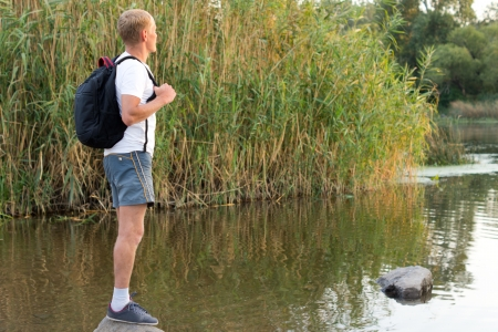 tranquillity: Man enjoying the tranquillity of nature standing on a rock overlooking a peaceful lake with a backpack on his back