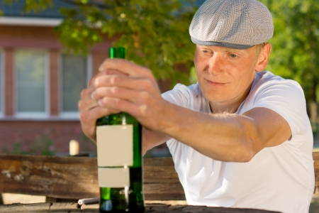 boozer: Alcoholic man feeling dizzy sitting at a table outdoors holding a bottle of wine Stock Photo