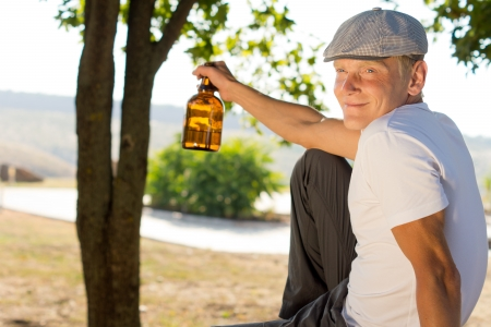 Happy drunk man with his bottle of booze or alcohol held in his hand sitting outdoors in a park smiling at the camera