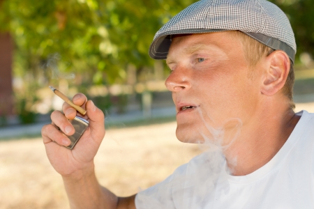 Man smoking a home rolled cigarette or joint of marijuana outdoors exhaling smoke through his mouth, closeup profile portrait