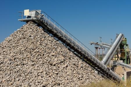 杭またはダンプに処理された押しつぶされた石を空にする、機械のベルトコンベアに建設業界のための石のキャスト鉱山を開く 写真素材