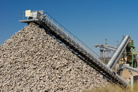 quarry: Open cast mining of stone for the construction industry with a mechanical conveyor belt emptying the processed crushed rock onto a pile or dump