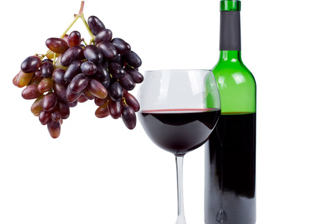 Bunch of fresh ripe red grapes hanging alongside a glass and unlabelled bottle of red wine in a conceptual image of wine making and ingredients, isolated on white photo
