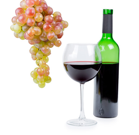 Unlabelled bottle and wineglass full of red wine with a bunch of fresh grapes hanging alongside them, conceptual of viticulture and wine making isolated on white photo