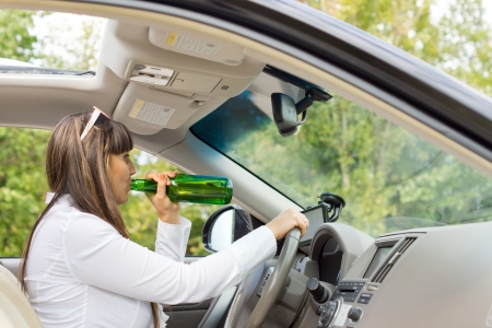 incapacitated: Side view from inside the vehicle of an alcoholic woman driver drinking and driving her car posing a threat to the safety of other motorists
