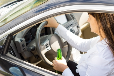 inebriated: Dangerous drunk and inebriated female driver holding her her steering wheel in one hand and bottle of alcohol in the other as she drives
