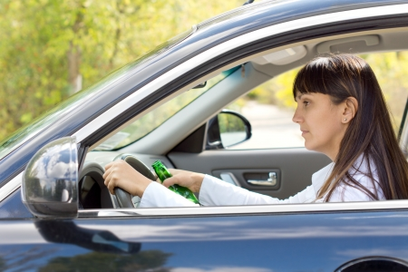 impaired: Drunk female driver with impaired ability staring blearily at her dashboard while gripping the wheel tightly and holding onto her bottle of alcohol