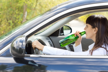 addictive drinking: Inebriated female driver drinking alcohol directly from the bottle as she steers her car along the road posing a danger to others