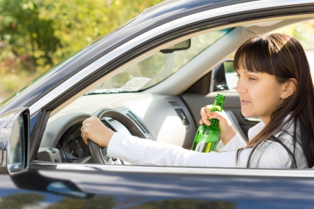 incapacitated: Happy inebriated female driver holding a botttle of alcohol and smiling at herself in the side view mirror oblivious of the road ahead