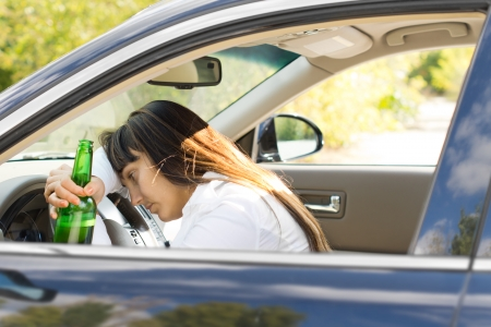 incapacitated: Incapacitated drunk woman driver leaning her head on the steering wheel while still gripping her bottle of booze