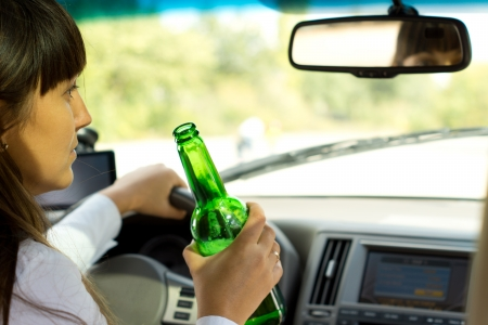 addictive drinking: Closeup view from behind of a drunken female driver sitting steering the car while holding a bottle of booze and staring morosely ahead