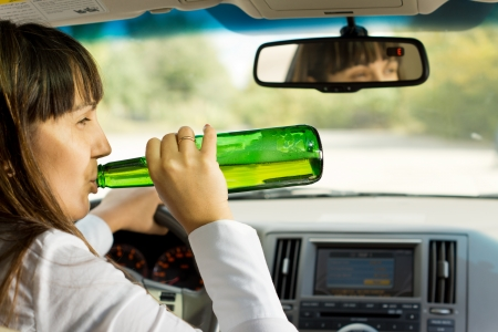 Intoxicated woman drinking and driving as she swigs alcohol from the bottle while driving down the road Stock Photo - 22519992