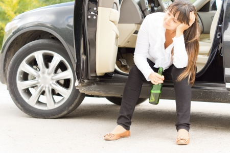 addictive drinking: Alcoholic female enjoying a lonely drink sitting in the open door of her parked car with a bottle of booze staring despondently into the distance Stock Photo