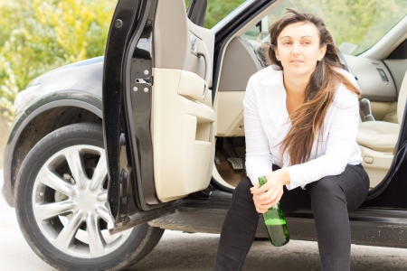 Lonely unhappy drunk woman sitting at the roadside in her parked car drinking alcohol directly from the bottle Stock Photo - 22520031