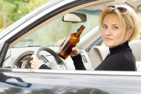 incapacitated: Intoxicated woman driver looking out of her side window with a serious expression as she drives by holding a bottle of booze in her hand