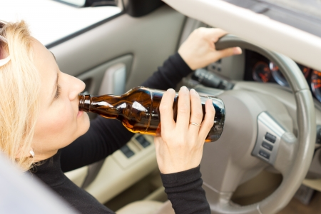 incapacitated: High angle view of a drunk woman driver sitting behind her steering wheel imbibing from a bottle of alcohol as she drives