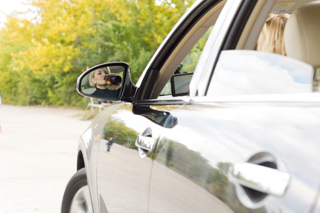 Woman weaving her car on the road as she drinks alcohol directly from a bottle as seen in the reflection in her side view mirror Stock Photo - 22520038