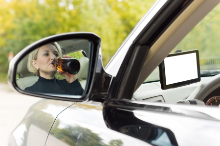 Reflection in the side view mirror of the car of an alcoholic female driver drinking as she drives along the road sipping directly from a bottle of spirits Stock Photo - 22520039