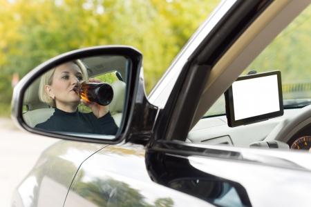 Reflejo en el espejo de la vista lateral del coche de una bebida alcoh�lica mujer piloto mientras conduce por la carretera bebiendo directamente de una botella de licor Foto de archivo