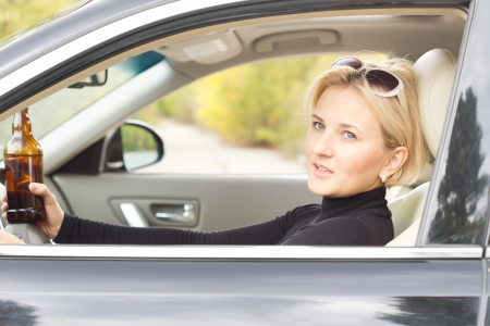 incapacitated: Stylish female drunkard holding her bottle of alcohol as she drives along the road in her car looking out of the side window as she passes Stock Photo