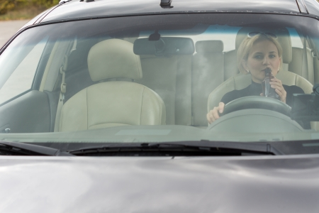 incapacitated: View through the front windscreen of a female driver drinking alcohol from a bottle in the car while driving along the road Stock Photo