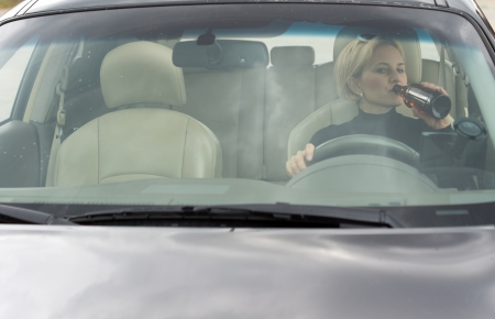 incapacitated: Female alcoholic sitting in her car drinking and driving as she gulps alcohol directly from the bottle, view through the front windscreen