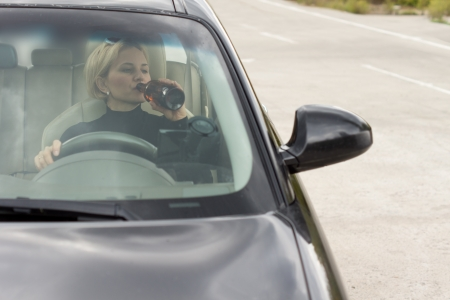 incapacitated: View through the front windscreen of a drunk woman driving and drinking alcohol from a bottle while travelling on the road