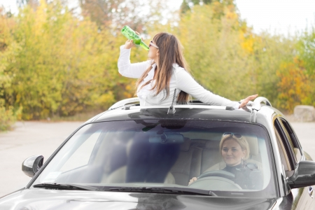 sunroof: Drunk woman passenger in a car standing up through a sunroof drinking alcohol directly from a bottle as she continues her partying on the way home Stock Photo