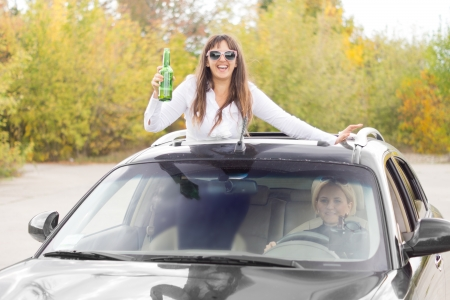 sunroof: Laughing drunk female car passenger standing up on the seat through the sunroof waving her bottle of alcohol while being driven by a friend Stock Photo