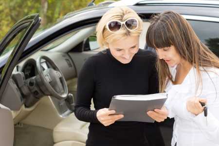 saleslady: Blond woman smiling as she reads a contract for the purchase of her new car with the saleslady who is holding the ignition keys