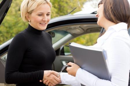 Felicitando Saleslady nuevo propietario de un autom�vil darle la mano y sonriendo con una mujer rubia atractiva, ya que cerrar el trato