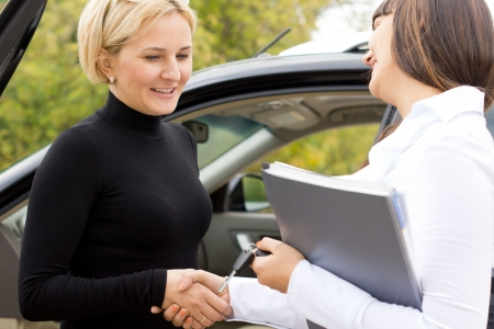 Saleslady congratulating a new car owner shaking hands and smiling with an attractive blond woman as they finalise the deal Stock Photo