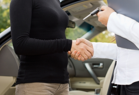 Close up view of the hands of two women shaking hands on a car purchase with one holding the contract and keys photo