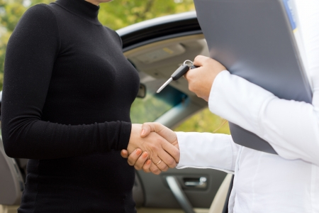 Two women shaking hands to finalise the deal on the sale of a new car with the saleslady holding the contract and keys in her hand photo