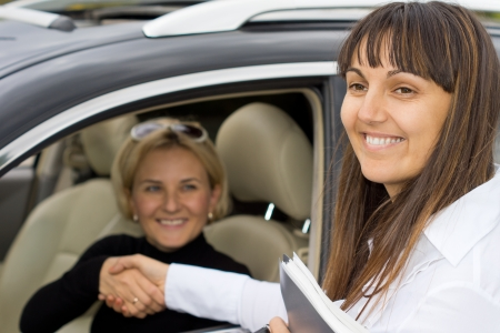 window seal: Smiling saleslady congratulating the new owner of a car as they shake hands to seal the deal through the open window of the vehicle Stock Photo