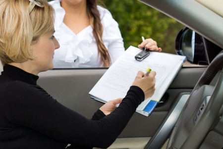 Blond female driver signing the deal on the purchase of a new car on the contact being held through the open window by the saleslady