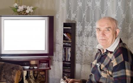 gente viendo television: Senior hombre viendo la televisión con una pantalla en blanco visible en el set mientras se vuelve a sonreír a la cámara