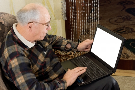 High angle view showing the blank screen of a balding senior man wearing glasses using a laptop computer to surf the web