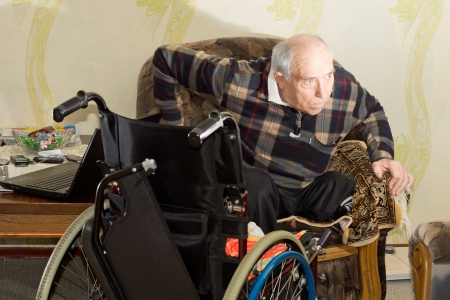 Disabled man changing from a chair to a wheelchair hoisting himself up out of the armchair with the wheelchair positioned in front of him as he displays his independence photo