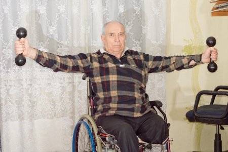 Disabled senior man with an amputated leg sitting in a wheelchair working out with dumbbells to strengthen his upper body and arms photo