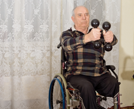 Senior handicapped man exercising with a pair of dumbbells to strengthen his arms while sitting in a wheelchair photo