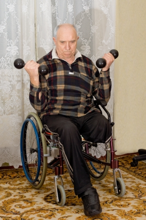 Senior disabled man sitting in his wheelchair exercising with dumbbells with a look of determination on his face as he lifts weights to strengthen his arm muscles photo